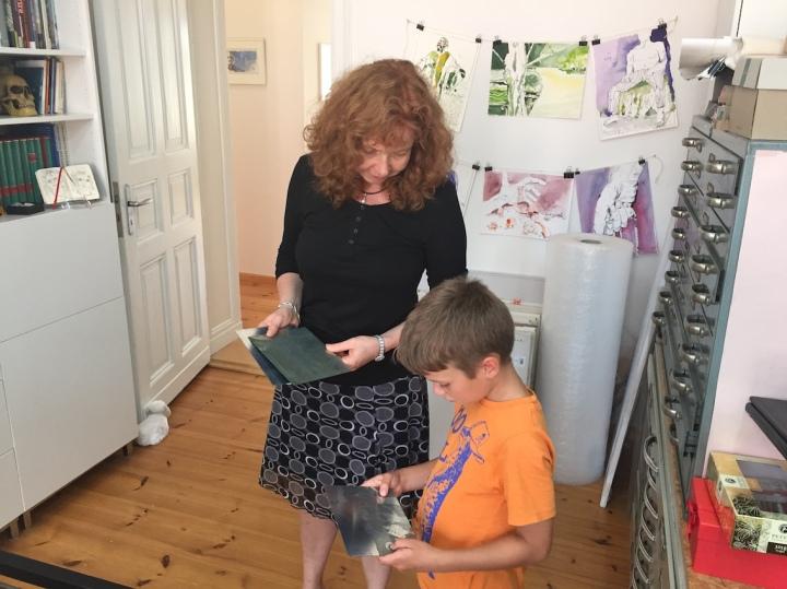 Die Künstlerin erklärt dem Kind, wie eine Radierung entsteht.